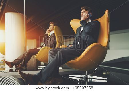 Laughing handsome male entrepreneur sitting in trendy armchair and speaking on his smartphone attractive man employer calling his colleague with cell telephone while sitting next to mirror in office
