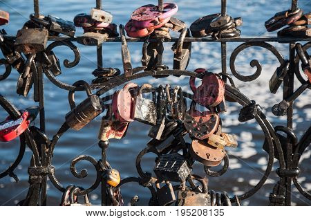 A Lot Of Wedding Padlocks Of Different Sizes And Shapes On The Curved Cast-iron Black Grate On The B