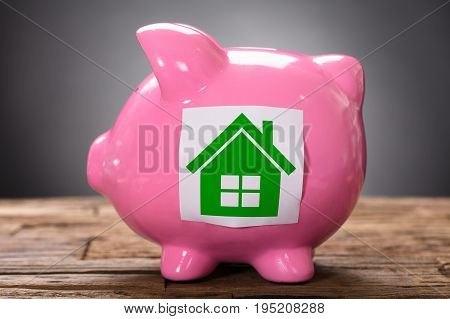 Closeup of green paper house on pink piggybank on wood