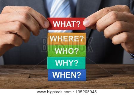 Closeup of businessman building blocks with question words on wood
