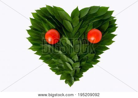 Heart From Green Leaves With Tomatoes. Still Life Resembles A Face. The Concept Of Love Of Nature An