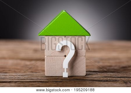 Closeup of small model house by question mark on wooden table