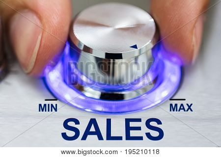 Cropped image of hand turning illuminated metallic knob by sales text