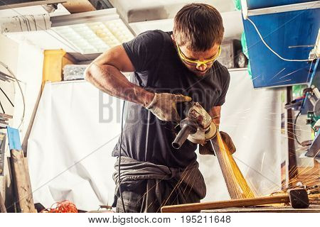 A young man welder in a black T-shirt goggles and construction gloves grinder metal an angle grinder in the garage in the background a lot of tools sparks fly to the side