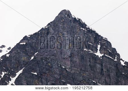 Sheer cliffside of a steep rocky mountain in Glacier National Park Montana USA.