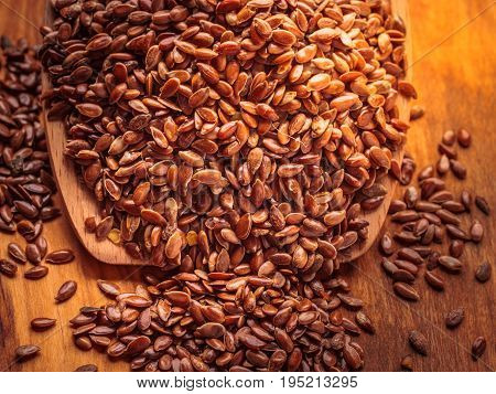 Healthy food for preventing heart diseases and overweight. Flax seeds linseed on wooden spoon wood background