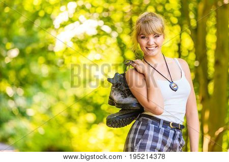 Adventure tourism active lifestyle. Hiking young woman in nature preparing for walk hike girl eholds trekking boots