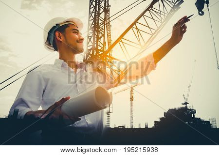 Double exposure of civil engineer holding blueprint with construction site.