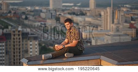 A man drinks coffee early in the morning on the roof. He looks away and thinks. Loneliness. In the background the city landscape
