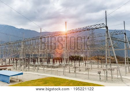 high voltage power transformer substation in valley against a cloudy sky