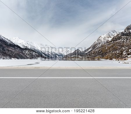empty road with snow mountain and ice lake in tibetan plateau