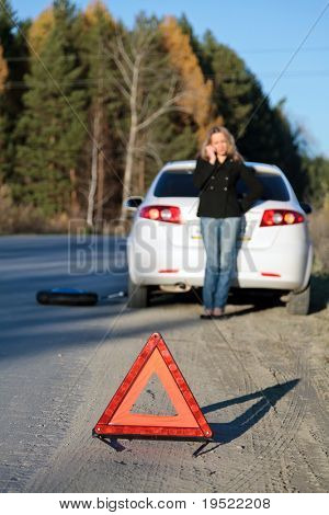Young woman standing by her damaged car and calling for help. Focus is on the red triangle sign. Shallow depth of view.