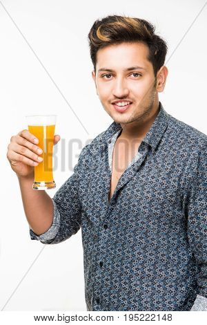 Young handsome Indian man in casual shirt drinking or a glass full of fresh orange juice or aerated drink for breakfast.
