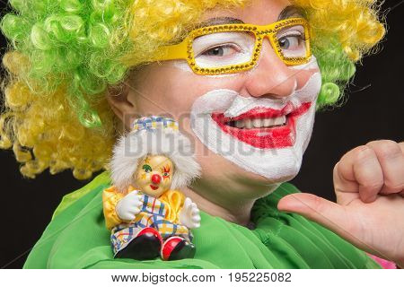 Good curly clown holding a beautiful little toy clown