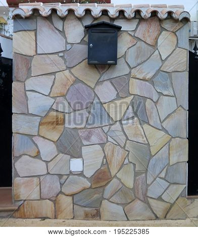 Letterbox on Stone clad wall in village in Andalusia Spain