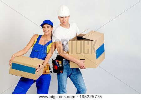 Portrait of a happy man and woman move to a new apartment, they carry boxes with things. Repair, construction and mortgage concept.