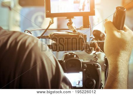 Cameraman with his video camera shooting, Hands Adjusting Camera,film production crew, behind the scenes background.
