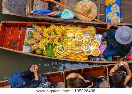 Traveler enjoying and take a photo with smartphone on long trail boat at Damnoen Saduak floating market in Ratchaburi near Bangkok Thailand