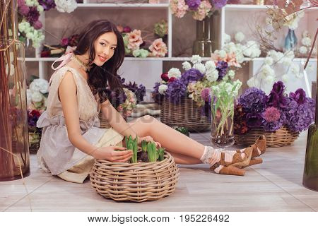Playful fashion model looking and touching many spring flowers. Beautiful girl in tender white dress sitting on the floor against floral background in flower shop. Joyful asian female florist happy smiling and looking at camera.