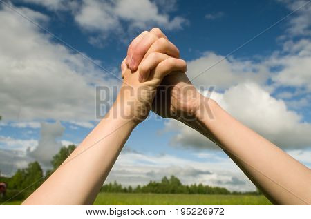 Two teenagers linked hands in triangle shape on the background of the summer sky.