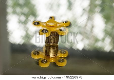 Spinner located on a stack of shiny coins the mirror rotates to a shimmering light background.