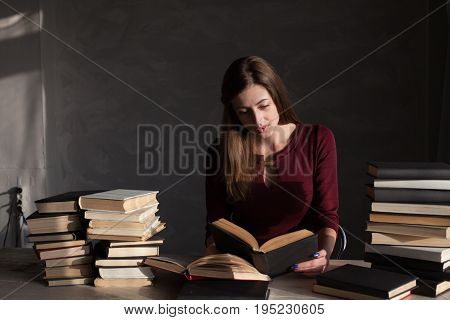 the girl sitting at the table reading a lot of books library