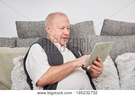 Senior citizen with tablet computer learns about technology