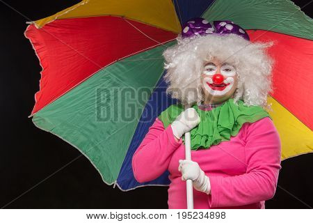 Jolly funny clown with a multi-colored umbrella on a black background