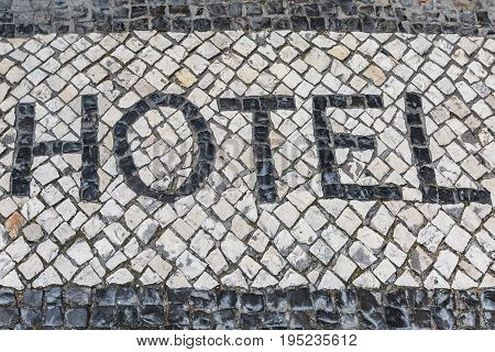Word Hotel on a Typical Decorative Mosaic Floor in Lisbon Street Portugal