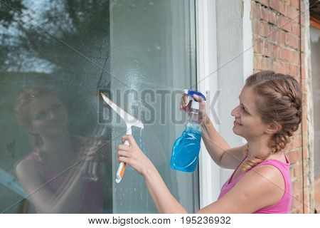Beautiful young girl with pigtails washes a window in a brick house