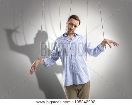 Portrait Of Sad Man On Manipulating Ropes With Shadow Of Puppeteer Behind Isolated On Grey