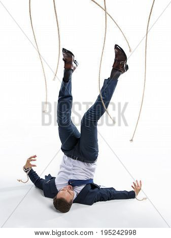 Businessman In Suit Got Out Of Manipulating Ropes Isolated On White