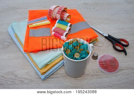 Sewing tools and sewing kit on wooden textured background. Sewing kit. Thread needles and cloth. tailor workspace with sewing and handmade tools
