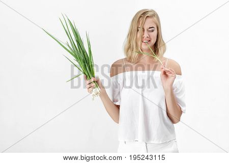 Beautiful blond woman in a white blouse eating green bitter onion on a white background. Health and vitamins