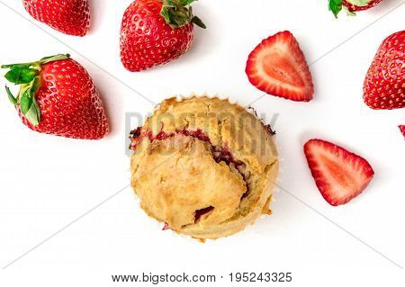 An overhead photo of a strawberry muffin with slices of strawberries, shot from above on a white background with a place for text. Selective focus