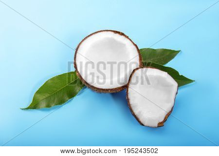 A close-up colorful cut coconuts on a bright light blue background. Coconut cracked into pieces and fresh leaves. Exotic fruits for vegan diet. Healthy lifestyle.