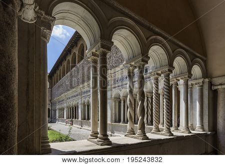 Basilica di San Giovanni in Laterano (St. John Lateran basilica). Inner patio surrounded by graceful twisted columns of inlaid marble. Italy Rome June 2017