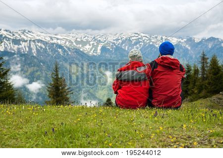 Couple Of Travelers Sit, Embracing In An Alpine Meadow