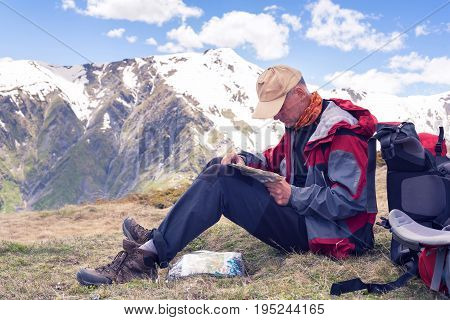 Concentrated Man Traveler Sits In The Mountain Plateau