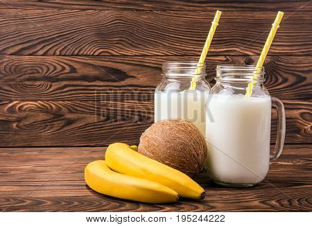 A bright set of fruits and milk on a brown wooden background. Delicious yellow bananas and a hard tasty coconut. Two mason jars filled with fresh coco milk. Glasses with striped straws.