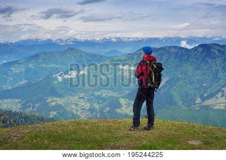 Man Traveler Admires A Panorama Of Mountains