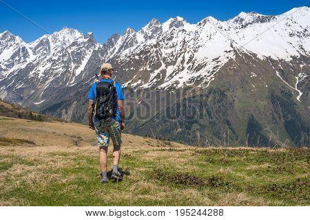 Man Hiker Goes Along Alpine Meadow