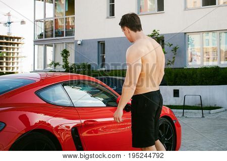 Handsome Sexy Male Athlete Man With Naked Torso In Yard Of House In Parking Lot Near An Expensive Pr