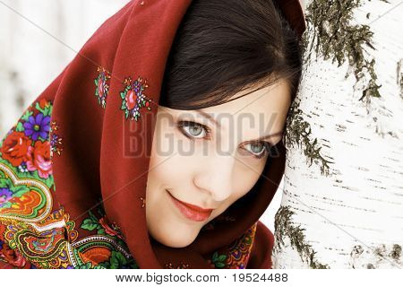Gorgeous woman in shawl on her head standing by the birch tree