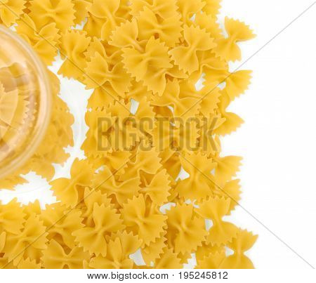 Uncooked Italian farfalle pasta, isolated on a white background. Raw pasta is scattered around the trasparent glass. Macaroni, noodle, pasta, spaghetti on a light background. Flour products.