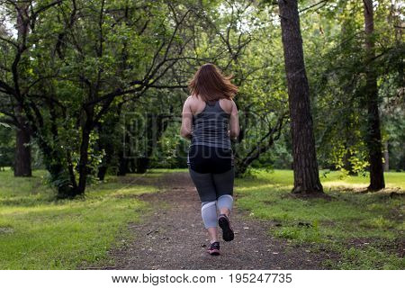 Overweight woman back running in the park . Weight loss concept.