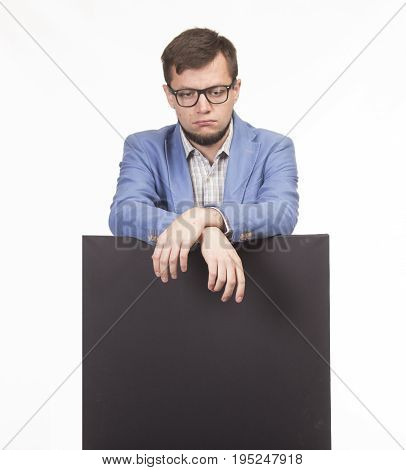 Young sad man portrait of a confident businessman showing presentation, pointing paper placard gray background. Ideal for banners, registration forms, presentation, landings, presenting concept.
