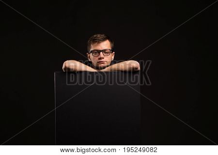 Young bored man portrait of a confident businessman showing presentation, pointing paper placard black background. Ideal for banners, registration forms, presentation, landings, presenting concept.