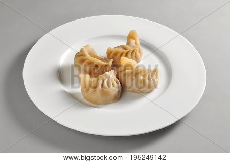 Round dish with Chinese steamed ravioli Jiaozi isolated on grey background