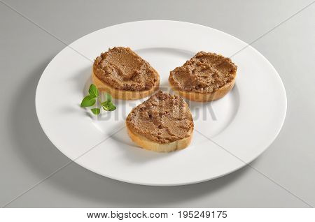 Round dish with Tuscan liver pate croutons isolated on grey background